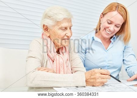 Elderly woman solves puzzles with daughter as memory training at home