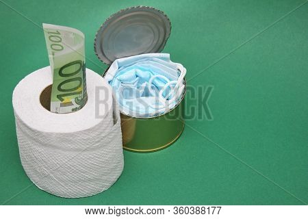 Medical Masks In A Can Next To A Roll Of Toilet Paper And A 100 Euro Bill In It. Concept Of Economic