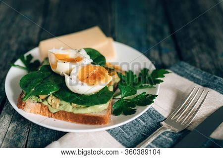 Toast With Avocado, Boiled Egg Spinach And Parsley On White Plate With Knife And Fork On Serviette A