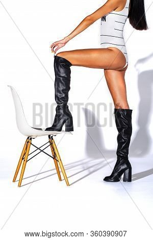 The Girl Stands Foot On A Tree Stool And Holds Her Boots By The Lock. Black Hessian Boots On The Fee