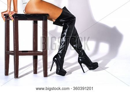Girl Sitting On A Chair Made Of Wood Dark Brown. Black Hessian Boots On The Feet Of A Model On A Whi