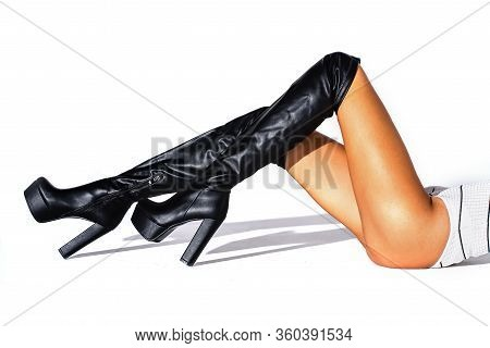 The Girl Lies On A White Background. Horizontal Shot. Black Hessian Boots On The Feet Of A Model On
