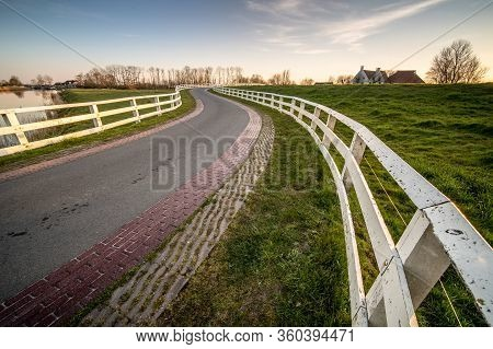 Curvy Road And White Fence In Old Dutch Countryside Near An Old Water Lock Leading Towards Historic