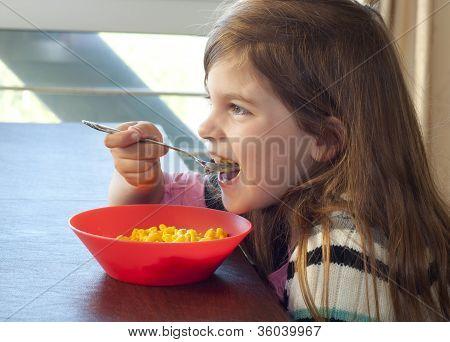 Young Girl Eating Macaroni And Cheese