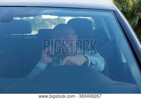Front Window View Handsome Young Man Talking On Mobile Phone While Driving His Car . Risky, Reckless