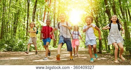 Happy kids run together to summer camp in nature