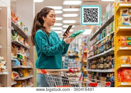 A Young Beautiful Caucasian Woman Reads The Qr Code Information Using Her Smartphone. Qr-code Icon A