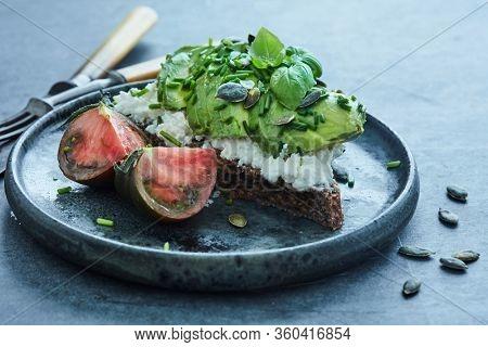 Avocado open sandwich with cream cheese, fresh herbs and pumpkin seeds