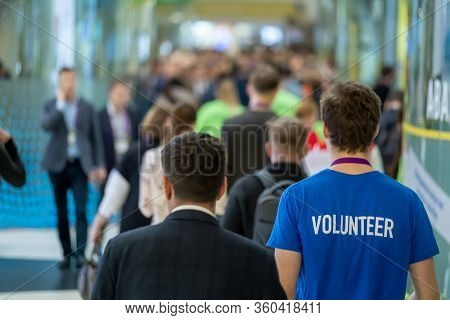 Crowd of people walking indoors, defocused, faces are not recognized