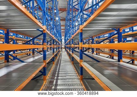 Empty Shelves In New Distribution Warehouse. Metal Equipment For Storage, Racks Blue Orange, Pallet