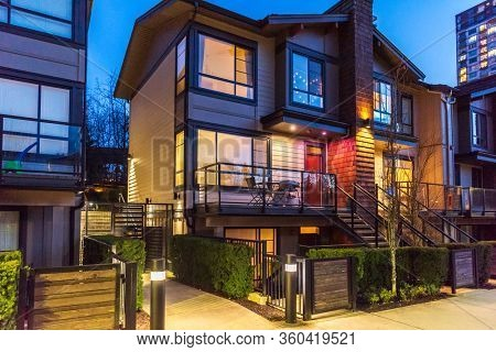 House building and city construction concept: night outdoor urban view of modern real estate homes.