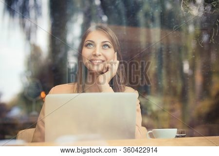 Daydreaming. Pensive Beautiful Woman With Coffee Mug Sitting Next To Window At Cafeteria