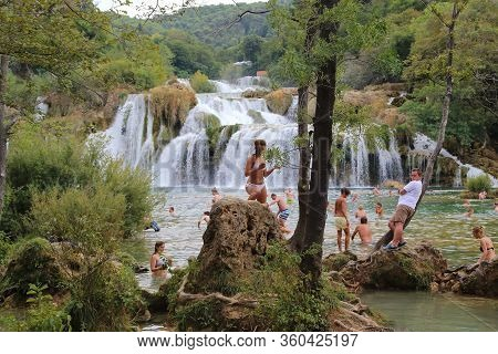 Skradin, Croatia - September 9, 2016: Unidentified People Bathe Under A Waterfall In A Designated Pl