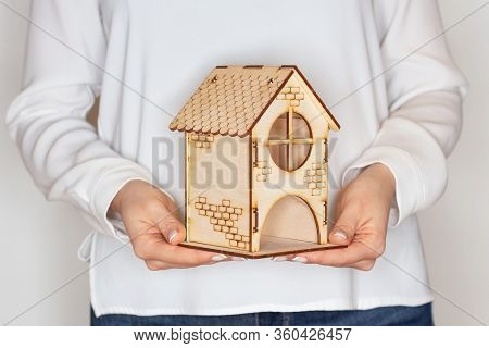 Stay At Home. A Woman Holds A Home In Her Hand. Concept Of Home Stay, Quarantine, Security Inside Th