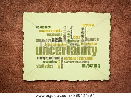 uncertainty and risk word cloud on a sheet of a soft handmade rag paper, business decision making and forecast concept