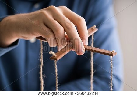 Person Manipulating Marionette With String