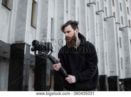 Bearded Professional Videographer In Black Hoodie Holding Professional Camera On 3-axis Gimbal Stabi