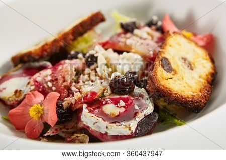 Buche de chevre with stewed pear and berry sauce. Food composition with french goat cheese and brioche. Haute cuisine dish served with flowers in plate. Delicious bakery meal on white table