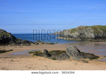 Porth Dafarch beach and cove with a fisherman going out on a kayak poster