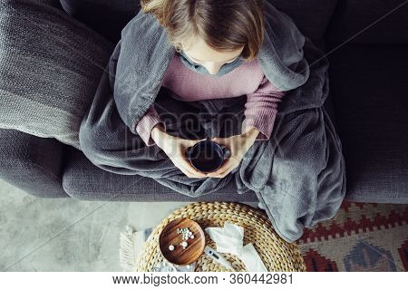Top View Of Sick Young Fair-haired Woman In Purple Sweater Covered With Grey Blanket Sitting On Grey