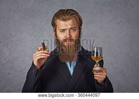 Boss Handsome Well-dressed Man Smokes Cigar With A Glass Of Drink In Hand Isolated Grey Background W