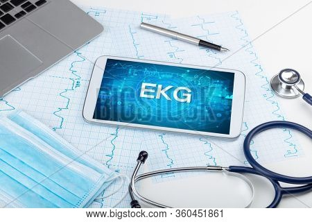 Close-up view of a tablet pc with EKG abbreviation, medical concept
