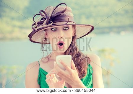 Closeup Portrait Surprised Young Woman In Hat Looking At Phone Seeing Unexpected News Or Photos With