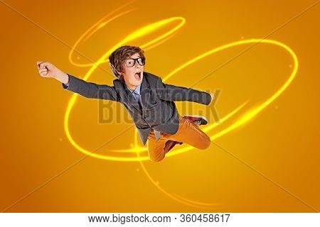 Educational concept. Funny smart boy teenager student flies through the air . Yellow background.