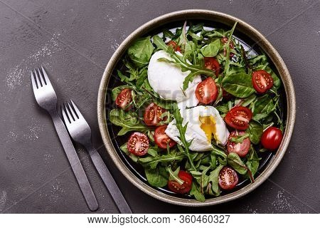Cherry Tomatoes, Poached Eggs And Herbs Mix Salad On Dark Background. Simple And Healthy Nutrition.