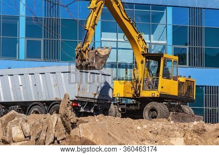 Excavator Loader And Dump Truck During Earthworks At A Construction Site. Loading Land In The Back O