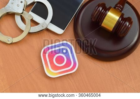 Instagram Paper Logo Lies With Wooden Judge Gavel, Smartphone And Handcuffs. Entertainment Lawsuit C