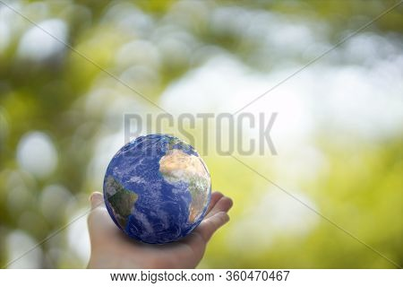 Plane Earth Globe Ball In Human Hand  On Green Sunny Background. Saving Environment, Save Clean Plan
