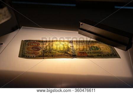 Checking The Hundred Dollar Bill For Fraud In Penetrating Light, Detection Of Luminescence Of Protec