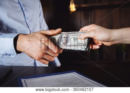 Man Offering Batch Of Hundred Dollar Bills. Hands Close Up. Venality, Bribe, Corruption Concept. Han