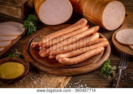 Fresh Sausages Served With Mustard On Wooden Cutting Board