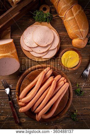 Flat Lay Of Deli Meat Slices And Frankfurter Sausages Served With Mustard On Vintage Wooden Backgrou