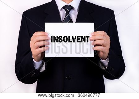 A Businessman Is Holding A Tablet With The Text Insolvent In Front Of Him In His Hands. Business Con