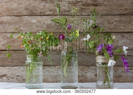 Meadow Natural Wildflowers Bouquets In Glass Jars And Bottles On Wooden Rustic Background. Herbal Me