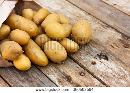 Raw Uncooked Organic Potatoes Spilling Out Of A Recycled Paper Bag Onto Natural Weathered Wooden Boa