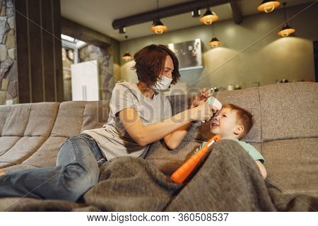 Mother With Littler Son Sitting At Home On Guarantine