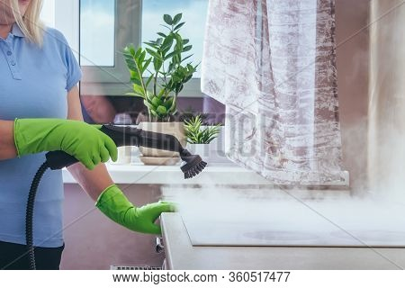 House Cleaning. Girl Brushes Steam Cleaners Kitchen White Electronic Parable Steam In Green Gloves.