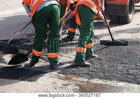 Workers On Asphalting Paver Machine During Road Street Repairing Works. Street Resurfacing. Fresh As