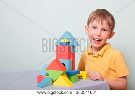 A Child Boy In A Yellow Polo Shirt Is Building A House Out Of A Color Constructor And Smiling, Isola