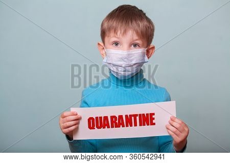 A Child In A Medical Mask Holds A Mockup With The Words Quarantine, Isolate On A Blue Background. Co