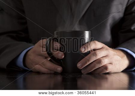 Executive Holds Steaming Coffee