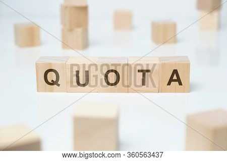 Modern Business Buzzword - Quota. Word On Wooden Blocks On A White Background. Close Up.