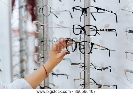 Choosing Glasses. Client In Optics. Selective Focus On Hand. Woman Touching Corrective Glasses On St