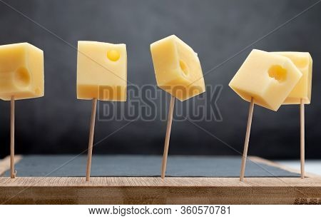 Portions (cubes, Dice) Of Emmental Swiss Cheese Punctured In Toothpicks.