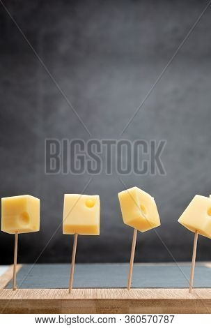 Portions (cubes, Dice) Of Emmental Swiss Cheese Punctured In Toothpicks. Copy Space.