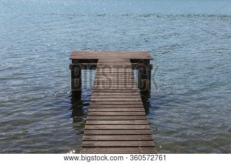 Wooden Pier Surrounded By The Blue Sea